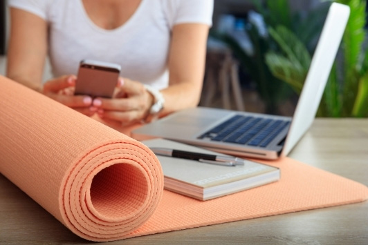 woman at desk with yoga mat