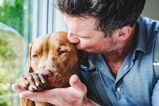 man kissing dog on head