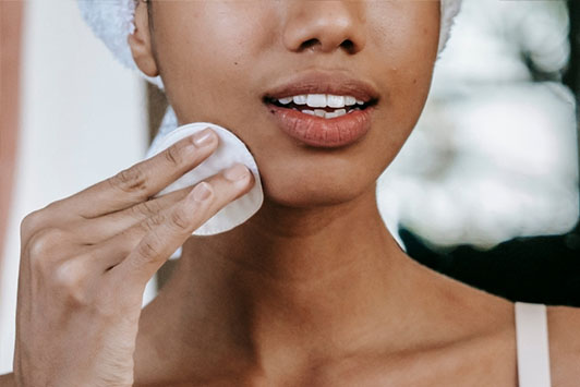 woman cleansing face with cotton pad