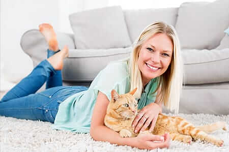 Girl playing with cat on rug