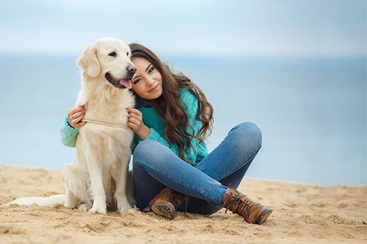Woman With Healthy Dog At Beach