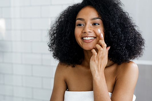 Woman Applies Face Cream With Hemp Seed Oil