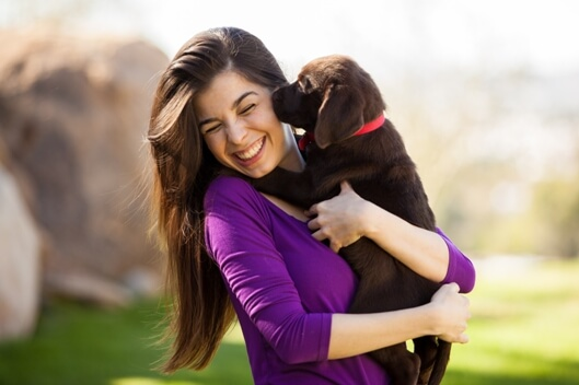 woman holding puppy smiling