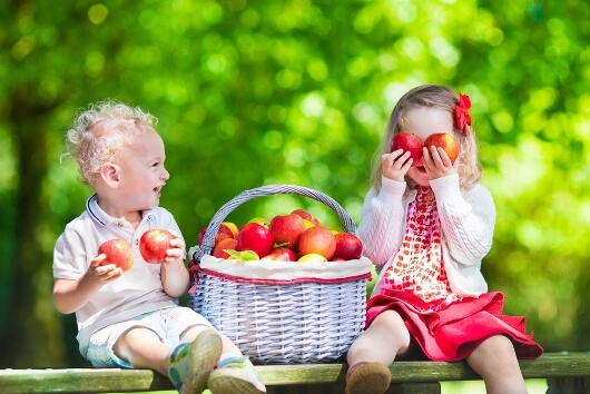 kids sitting with apples