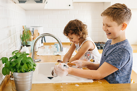 Brother And Sister Washing Dishes With Eco-Friendly Cleaner