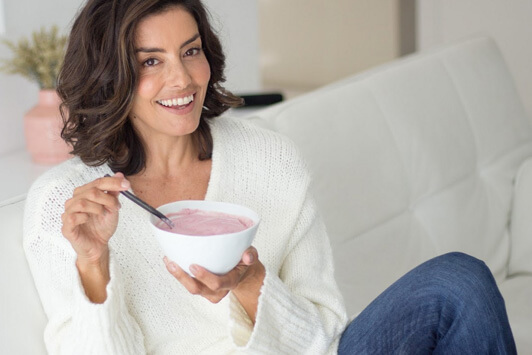 Woman Eating Vegan Berry Nice Cream On Couch